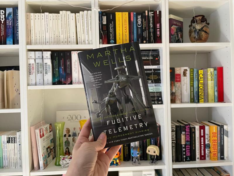 Fugitive Telemetry von Martha Wells vor Zockis Bücherregal.